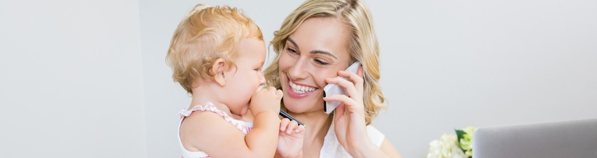 mother-talking-mobile-phone-while-holding-her-baby-girl