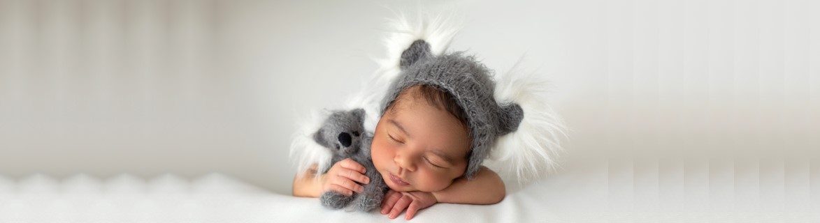 sleeping-infant-peacefully-laying-little-newborn-with-cute-grey-hat-toy-bear